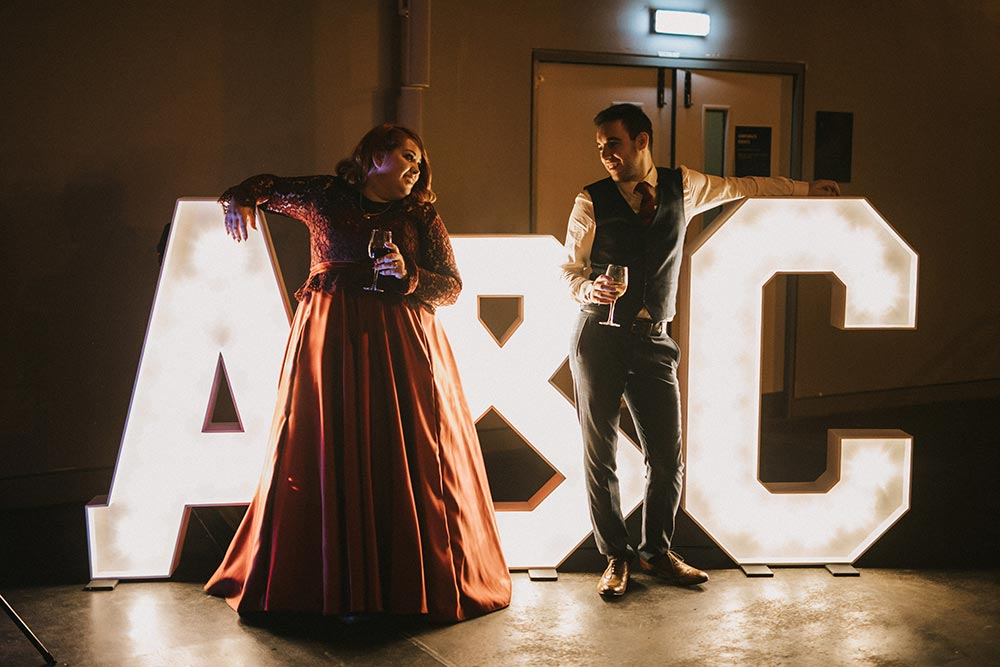 Bride and groom standing by their initials in large light up letters