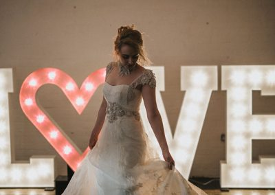 Bride in pretty dress in front of marquee lighted letters of LOVE with heart symbol from Ray of Light Letters, Lincolnshire and Yorkshire