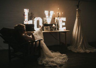 Bride relaxing with her feet up on table with Love light up letters