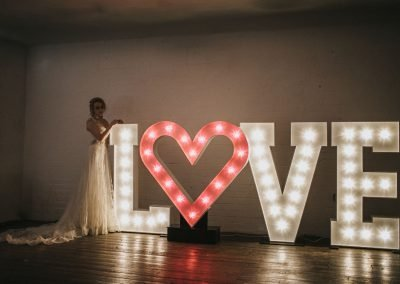 LOVE in large lighted letters with bride leaning on from Ray of Light Letters, Lincolnshire and Yorkshire