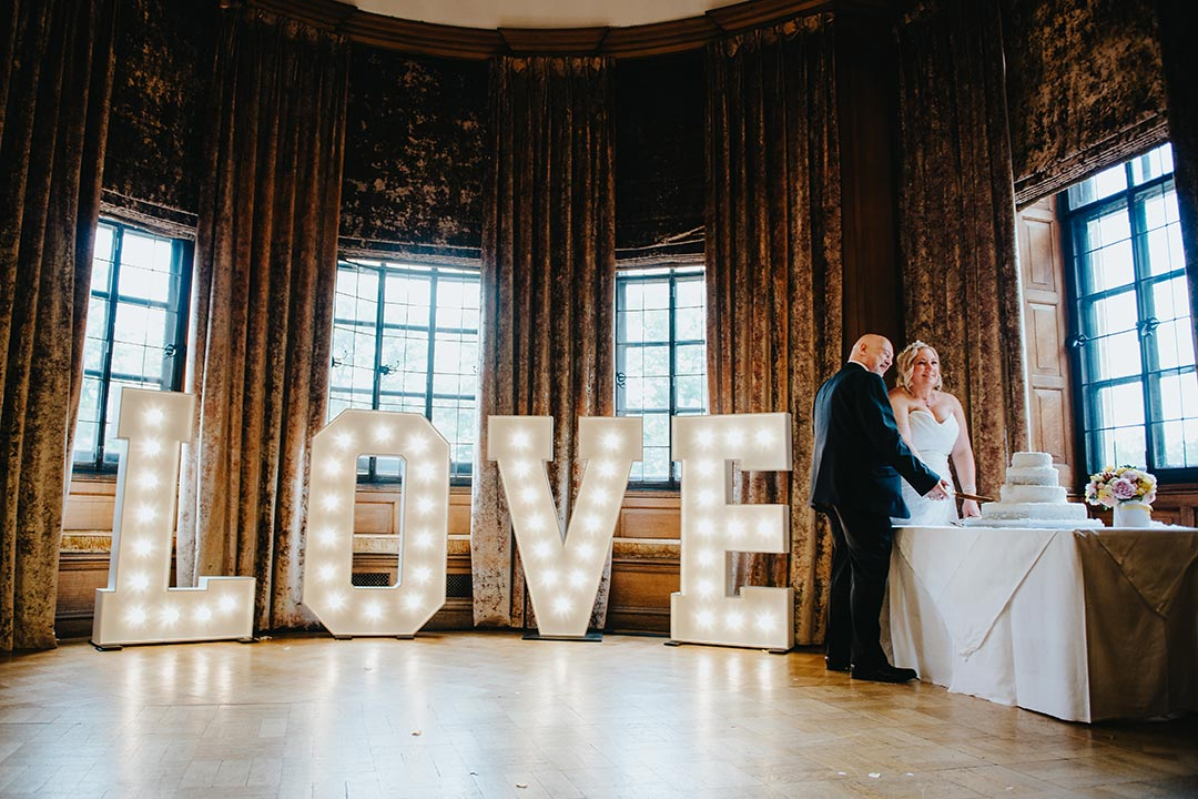 Bride and groom cutting cake at wedding next to lighted LOVE sign