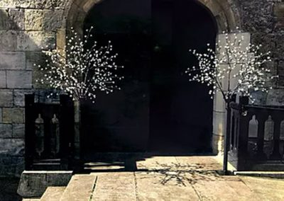 Pair of illuminated cherry blossom trees outside church for wedding