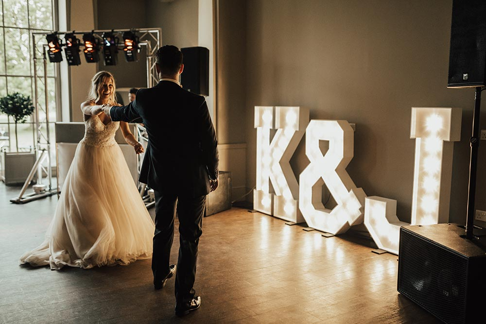 First dance with large lighted letters of initials next to DJ