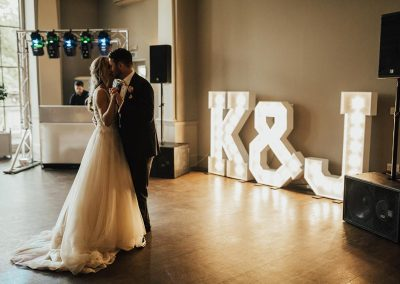 Wedding dance with large lighted letters of couple initials