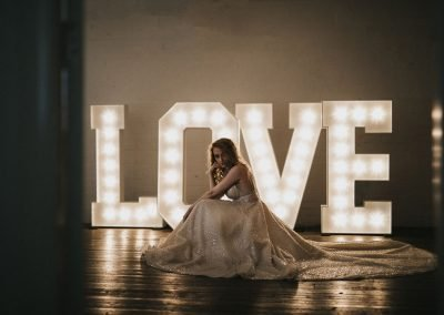 LOVE in large lighted letters with bride in front