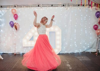 Lady dancing at her 40th birthday party in front of light up numbers