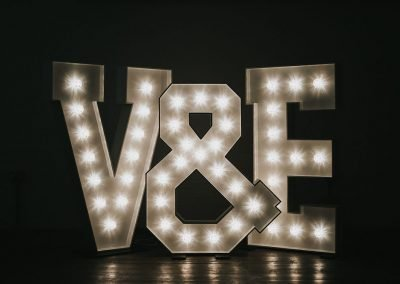 Initials in large lighted letters with ampersand
