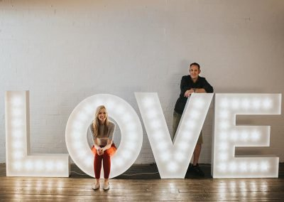 Rachel and Stephen from Ray of Light Letters with a large LOVE lighted sign