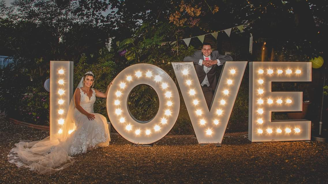 Bride and Groom with large marquee lighted letters of LOVE from Ray of Light Letters, Lincolnshire and Yorkshire